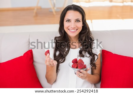 Pretty brunette eating strawberries on couch at home in the living room - stock photo