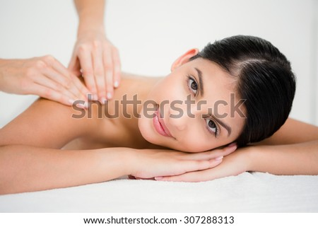 Pretty brunette enjoying a massage smiling at camera at the health spa