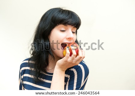 Pretty brunette girl biting red apple with close eyes on white background - stock photo