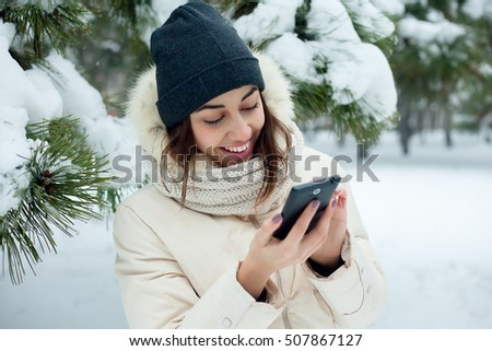 Pretty brunette girl doing a selfie with her smart phone.Beautiful young woman. Outdoor winter portrait. beautiful smiling girl talking on cell phone in snowy winter park