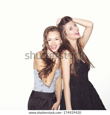 Pretty brunette girl friends having fun. Both looking at camera and smiling (laughing). Festive mood. Inside - stock photo