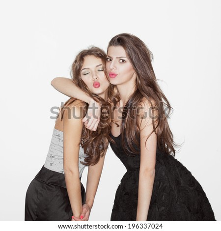 Pretty brunette girl friends having fun. Looking at camera and and showing kisses. One hugs another. Festive mood. Inside - stock photo