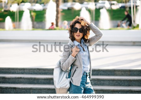 Pretty brunette girl  in sunglasses is posing to the camera in city.  She wears shirt, jeans, jacket and bag.  Her short hair is flying on wind.