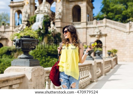 Pretty brunette girl in yellow T-shirt with yellow phone in sunglasses in park on sightseeing background. She holds red back and smiles to the side.