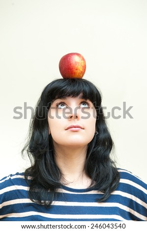 Pretty brunette girl looking red apple on her head on white background - stock photo