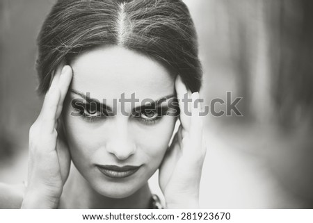 Pretty brunette girl touch her head, showing headache - stock photo