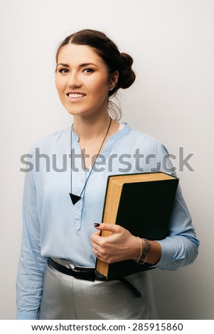 Pretty brunette girl with book in hand