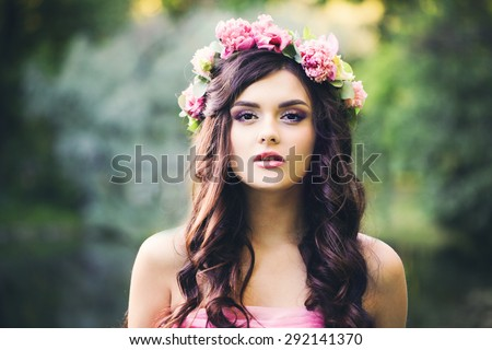 Pretty Brunette Girl with Curly Hairstyle Outdoors. Fashion Woman in Park. Makeup, Dark Wave Hair, Flowers - stock photo