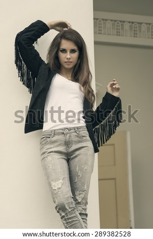 pretty brunette girl with urban modern style and strong stylish make-up in fashion pose near old column with charming expression  - stock photo