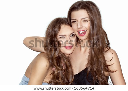 Pretty brunette girls with makeup and pink lips having fun. One showing tongue, winking and looking at camera. Other putting her head on shoulder of friend. Inside. Wearing dresses. - stock photo