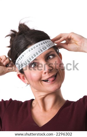 Pretty brunette holding a measuring tape around her head and pulling a face with her tongue out