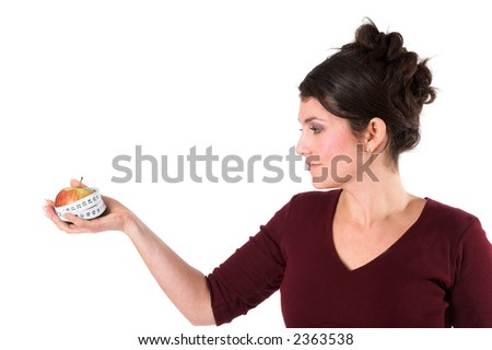Pretty brunette holding an apple out that is surrounded by measuring tape