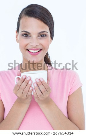 Pretty brunette holding coffee cup on white background