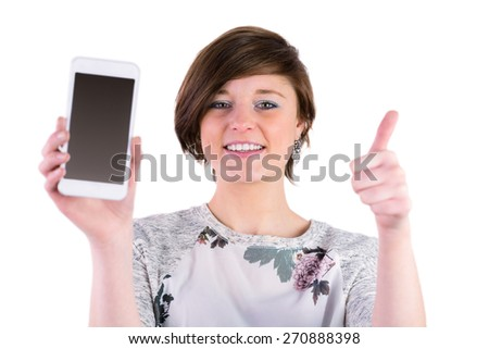 Pretty brunette holding her smartphone and looking at camera on white background - stock photo