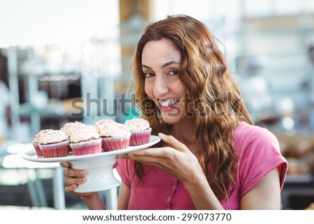 Pretty brunette holding plate of pastries at the bakery