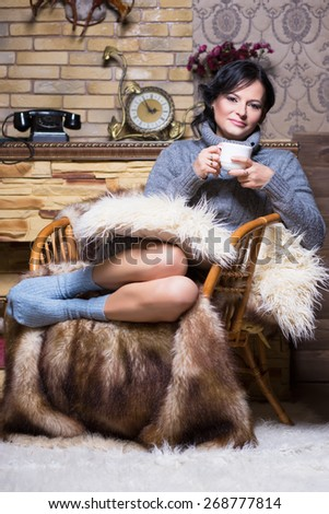 Pretty brunette in grey sweater and socks sitting on the chair with a cup - stock photo