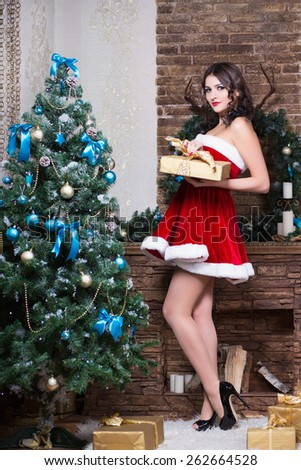 Pretty brunette in sexy red dress posing with a gift box near the fir-tree - stock photo