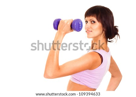 Pretty brunette in the gym doing exercises with dumbbells