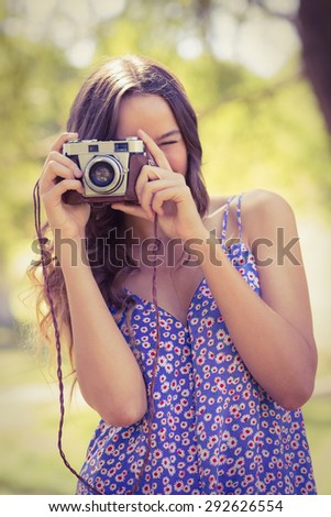 Pretty brunette in the park using retro camera on a sunny day - stock photo