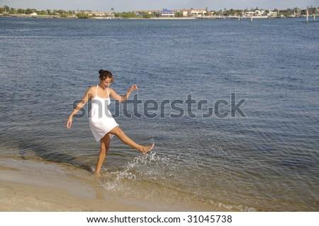 Pretty Brunette in white dress walking along the shore - stock photo