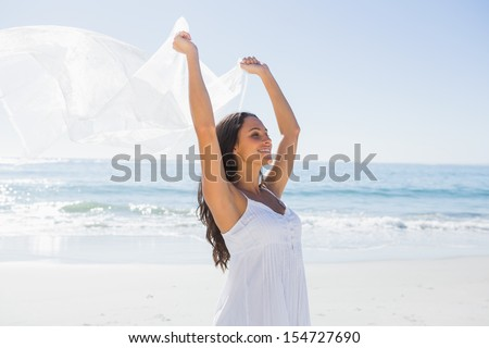 Pretty brunette in white sun dress holding sarong on the beach - stock photo