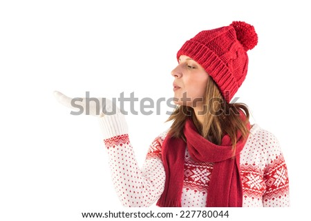 Pretty brunette in winter fashion blowing over hands on white background - stock photo