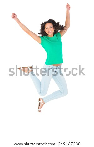 Pretty brunette jumping and smiling on white background
