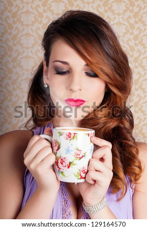 Pretty Brunette Lady Holding Warm Cup Of Coffee While Smelling The Aroma On Brown Vintage Background - stock photo