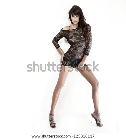 Pretty brunette lady with beautiful legs wearing short black dress and posing over white background