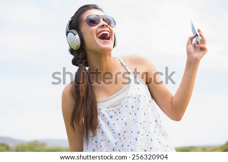 Pretty brunette listening to music on a sunny day - stock photo