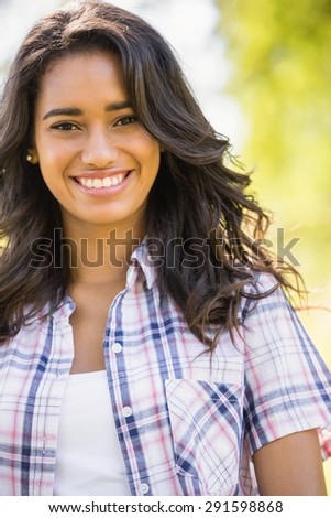 Pretty brunette looking at camera in the park on a sunny day - stock photo