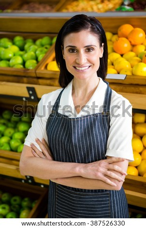 Pretty brunette looking at camera with arms crossed in supermarket