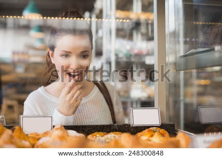 Pretty brunette looking at pastrys at the bakery - stock photo
