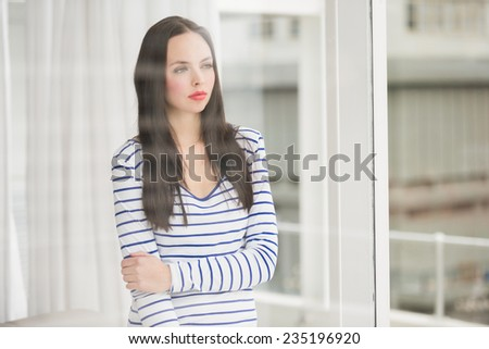 Pretty brunette looking out window at home in the living room - stock photo