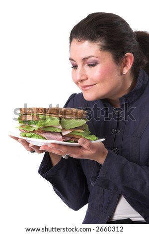 Pretty brunette looking to her sandwich, clearly looking forward to eating it