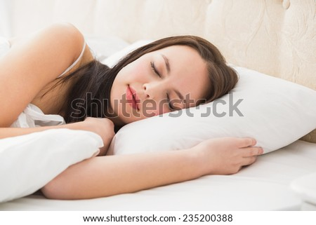 Pretty brunette lying in bed at home in the bedroom - stock photo
