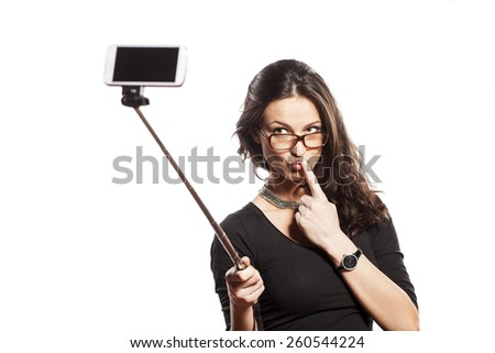 pretty brunette making selfie with a stick - stock photo