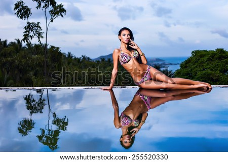 Pretty brunette model in mottled bikini posing at the pool with reflection of the evening sky - stock photo