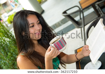 Pretty brunette model wearing turquoise singlet sitting by cafeteria table reading paper while enjoying coffee - stock photo