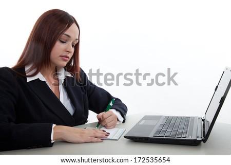 Pretty brunette native american writing check - stock photo