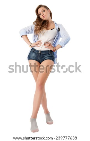 Pretty brunette posing in sexy jeans shorts on white background. - stock photo