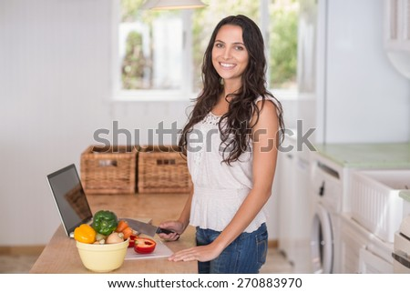 Pretty brunette preparing salad and using laptop in the kitchen - stock photo