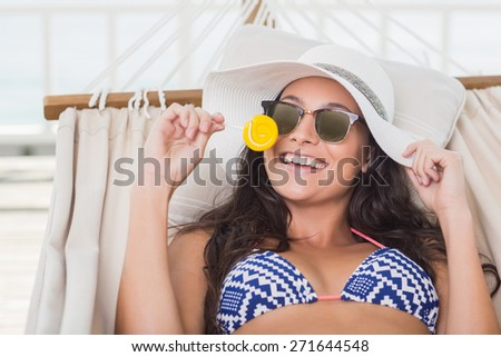 Pretty brunette relaxing on a hammock and eating a lollipop in patio - stock photo