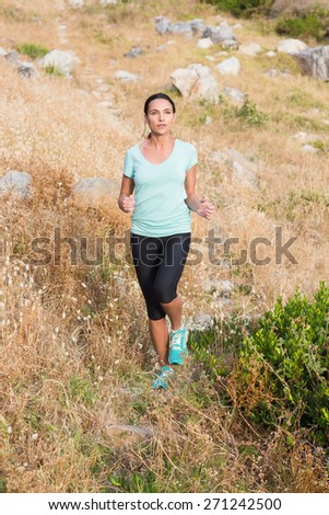 Pretty brunette running in the countryside