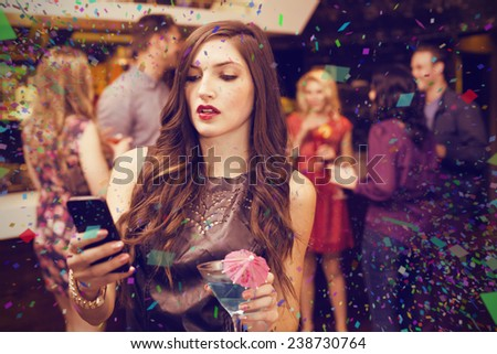 Pretty brunette sending a text against flying colours - stock photo