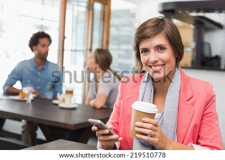 Pretty brunette sending a text drinking coffee at the coffee shop - stock photo