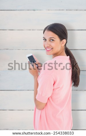 Pretty brunette sending a text message against wooden planks