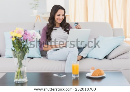 Pretty brunette shopping online with laptop at home in the living room - stock photo