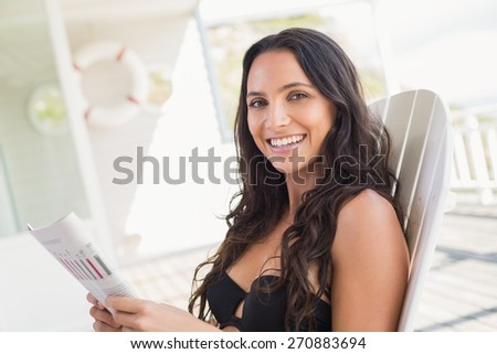 Pretty brunette sitting on a chair and reading magazine in patio - stock photo