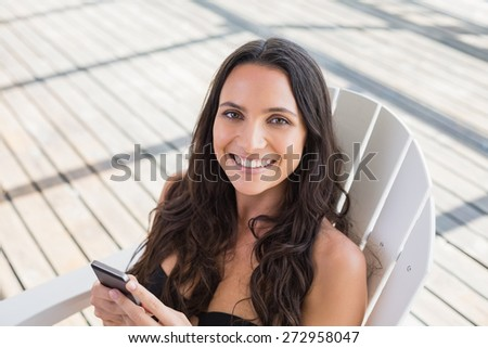 Pretty brunette sitting on a chair and texting with her mobile phone in patio